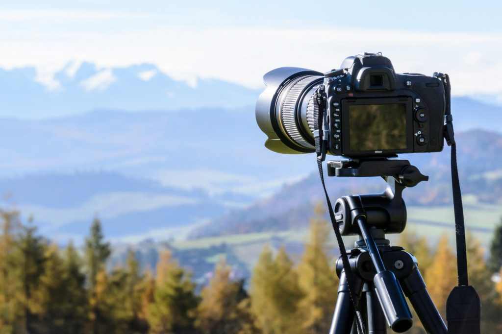black dslr mounted on tripod taking pictures of mountains and trees